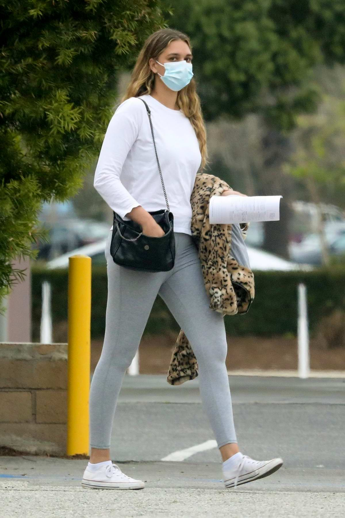 April Love Geary sports a white shirt, grey leggings and a mask as she leaves the Urgent Care in Malibu, California