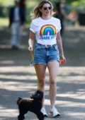 Ashley James looks trendy in denim shorts and a NHS tee while out to walk her dog at a local park in London, UK