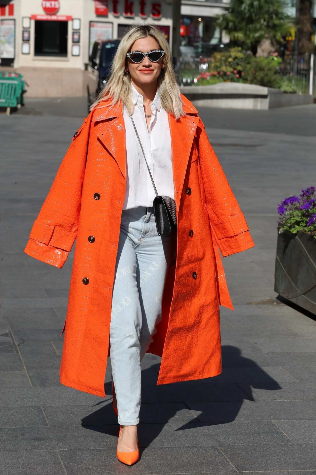 Ashley Roberts stands out in bright orange as she leaves Global Studios in London, UK