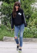 Dakota Johnson looks trendy in a hoodie and ripped jeans as while out for stroll in Los Angeles