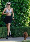 Devon Windsor sports a crop top and bike shorts while out for a run in Miami, Florida