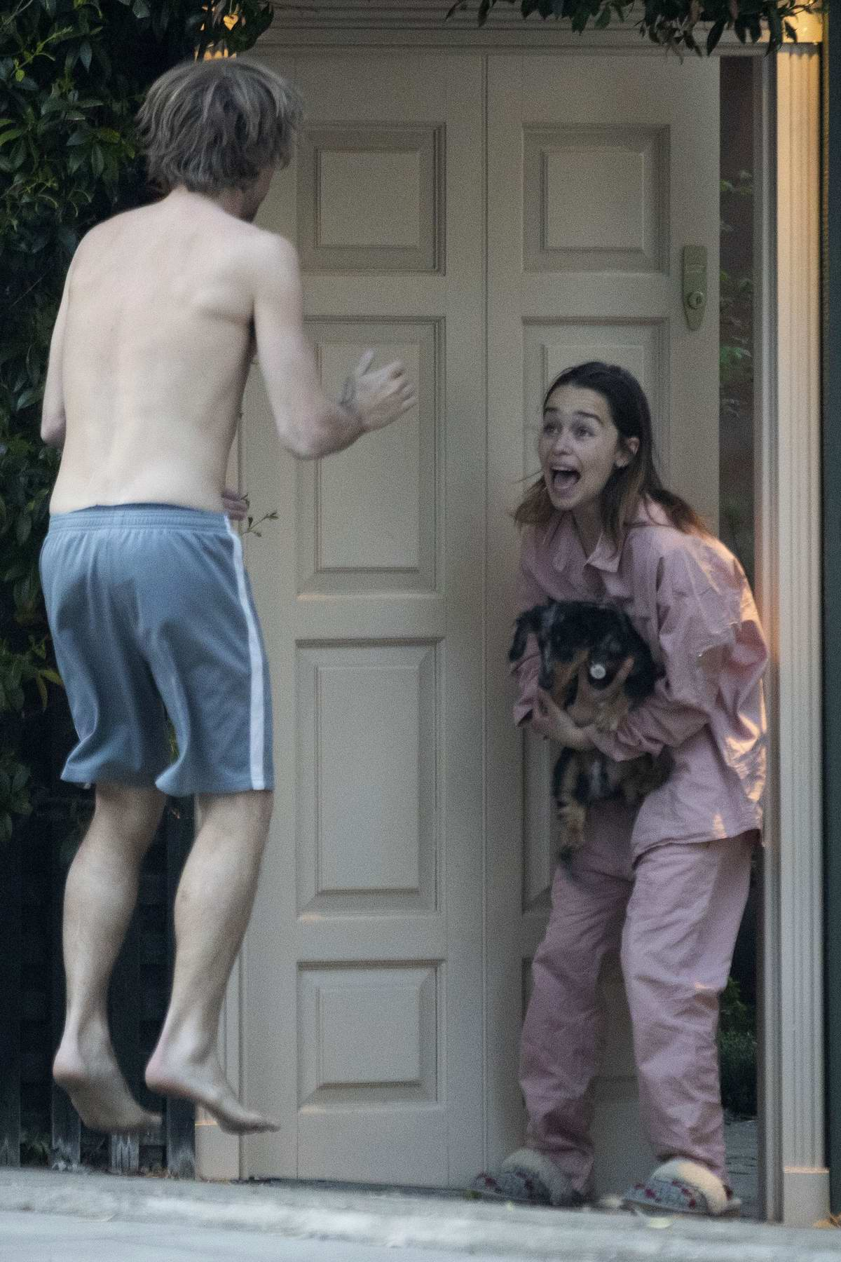 Emilia Clarke seen in pajamas cradling her dog while joining clap for NHS workers with mystery man in London, UK