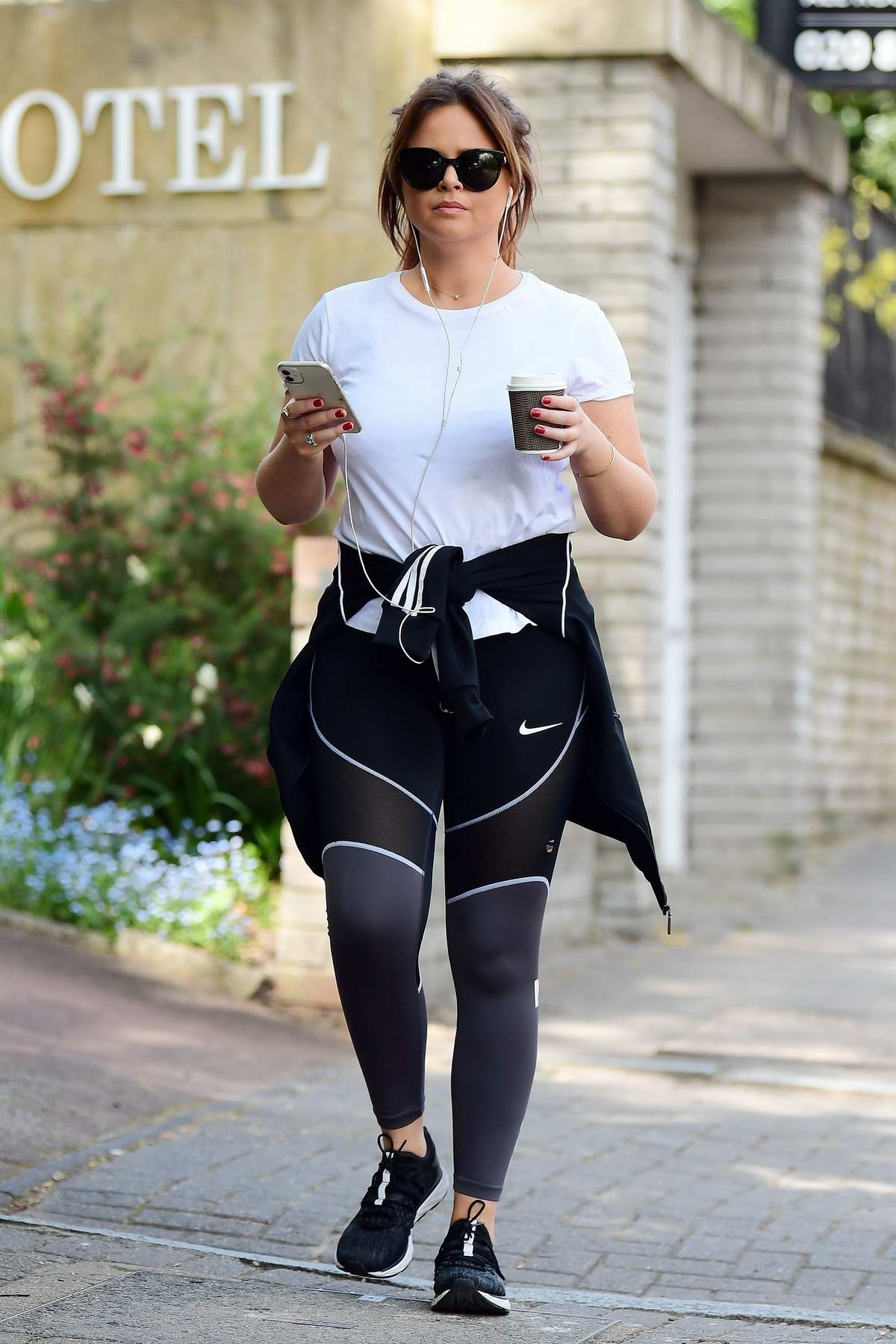 Emily Atack sports a white top and Nike leggings while out for a walk during the lockdown in London, UK