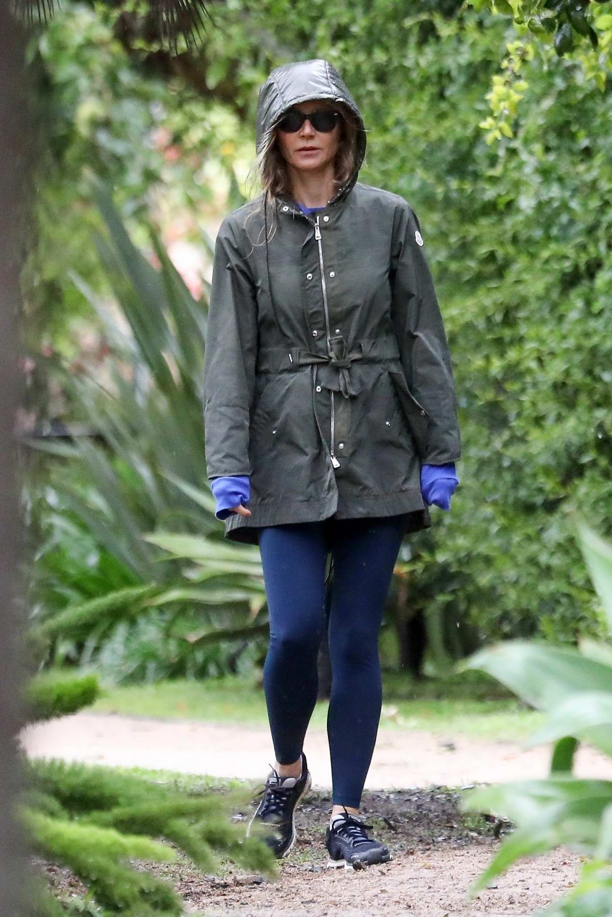 Gwyneth Paltrow wears a hooded jacket while out for a walk on a rainy day with Brad Falchuk in Brentwood, California