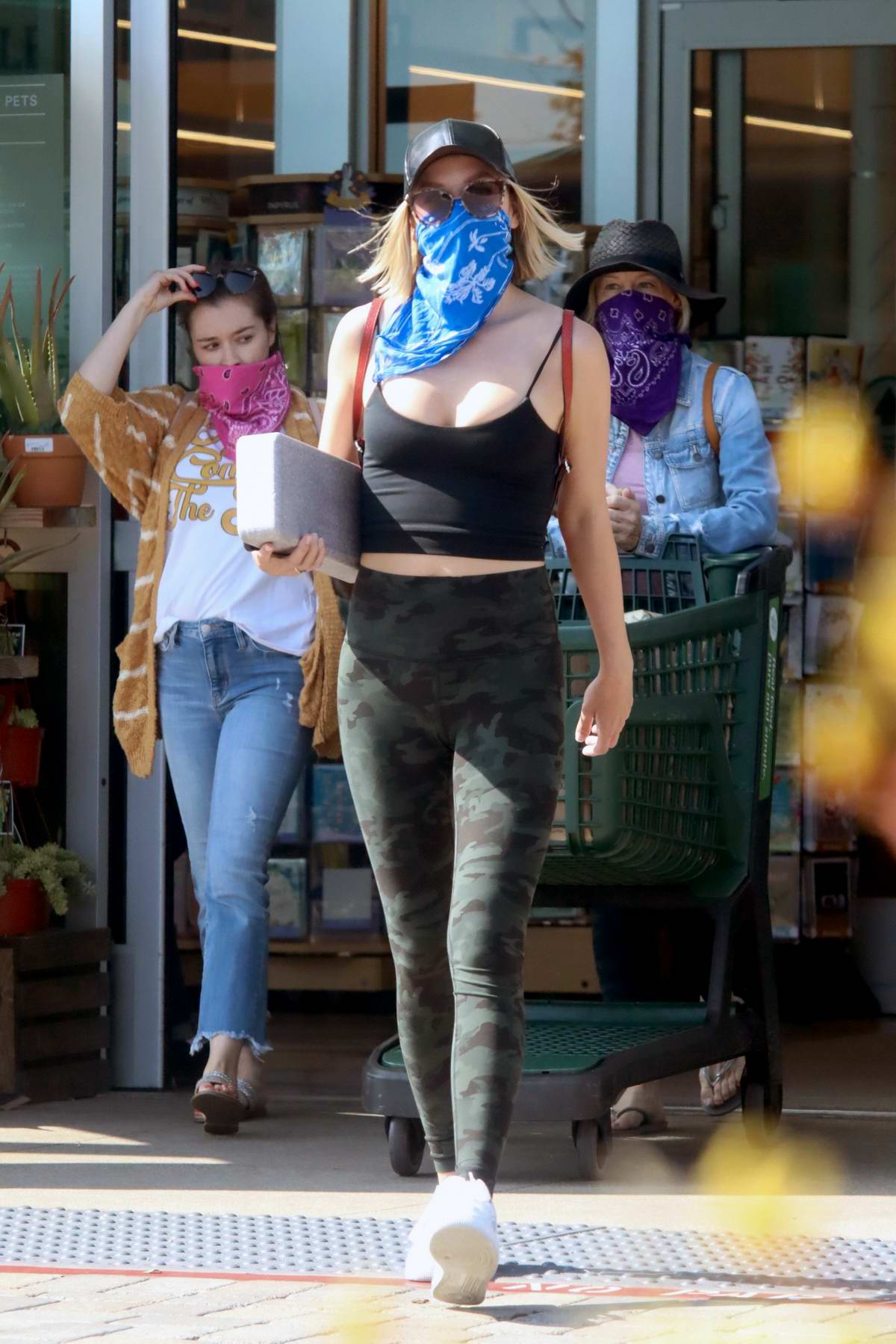 Julianne Hough wears a bandana mask with a black crop top and camo leggings while shopping at Whole Foods in Malibu, California