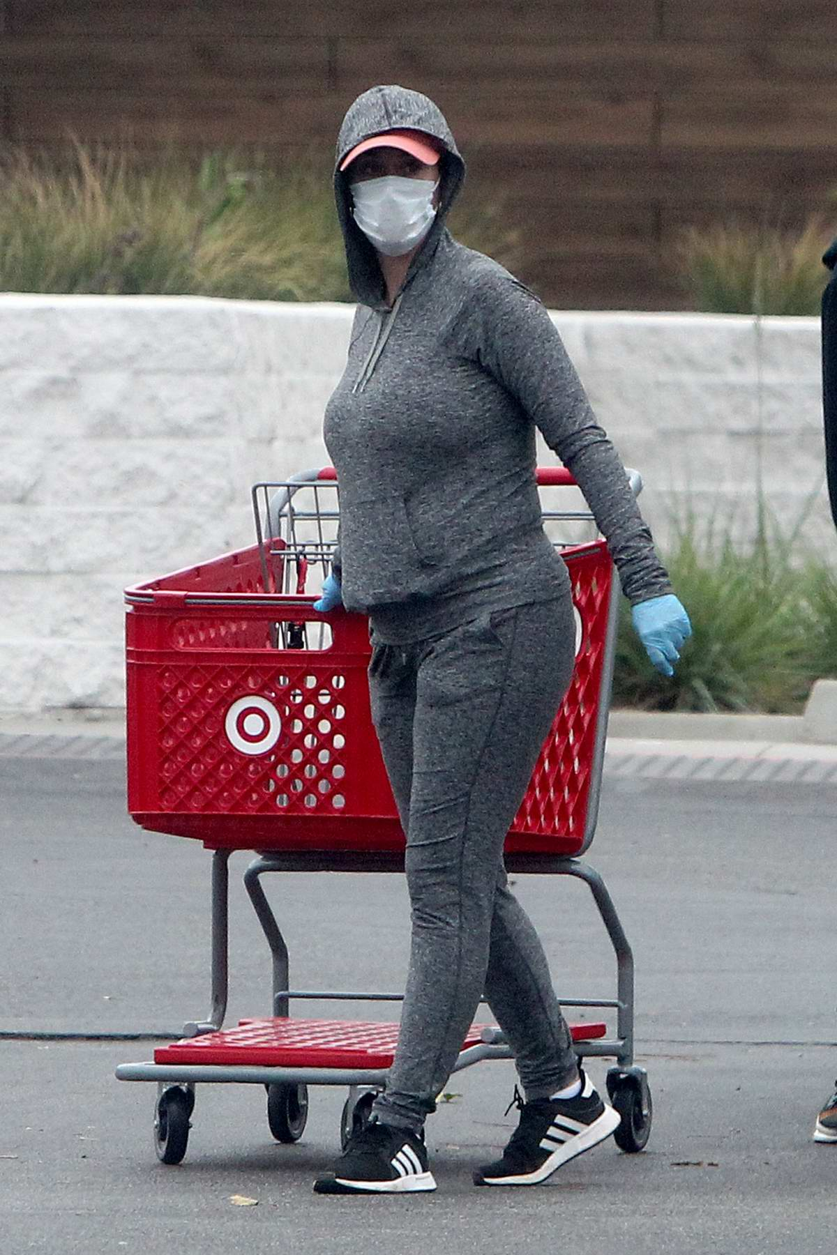 Katy Perry sports grey hoodie, leggings, and a mask while shopping for supplies with Orlando Bloom at Target in Los Angeles