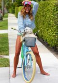 Kelly Bensimon plays with her dog Fluffy while on a bike ride as she keeps busy at home in West Palm Beach, Florida