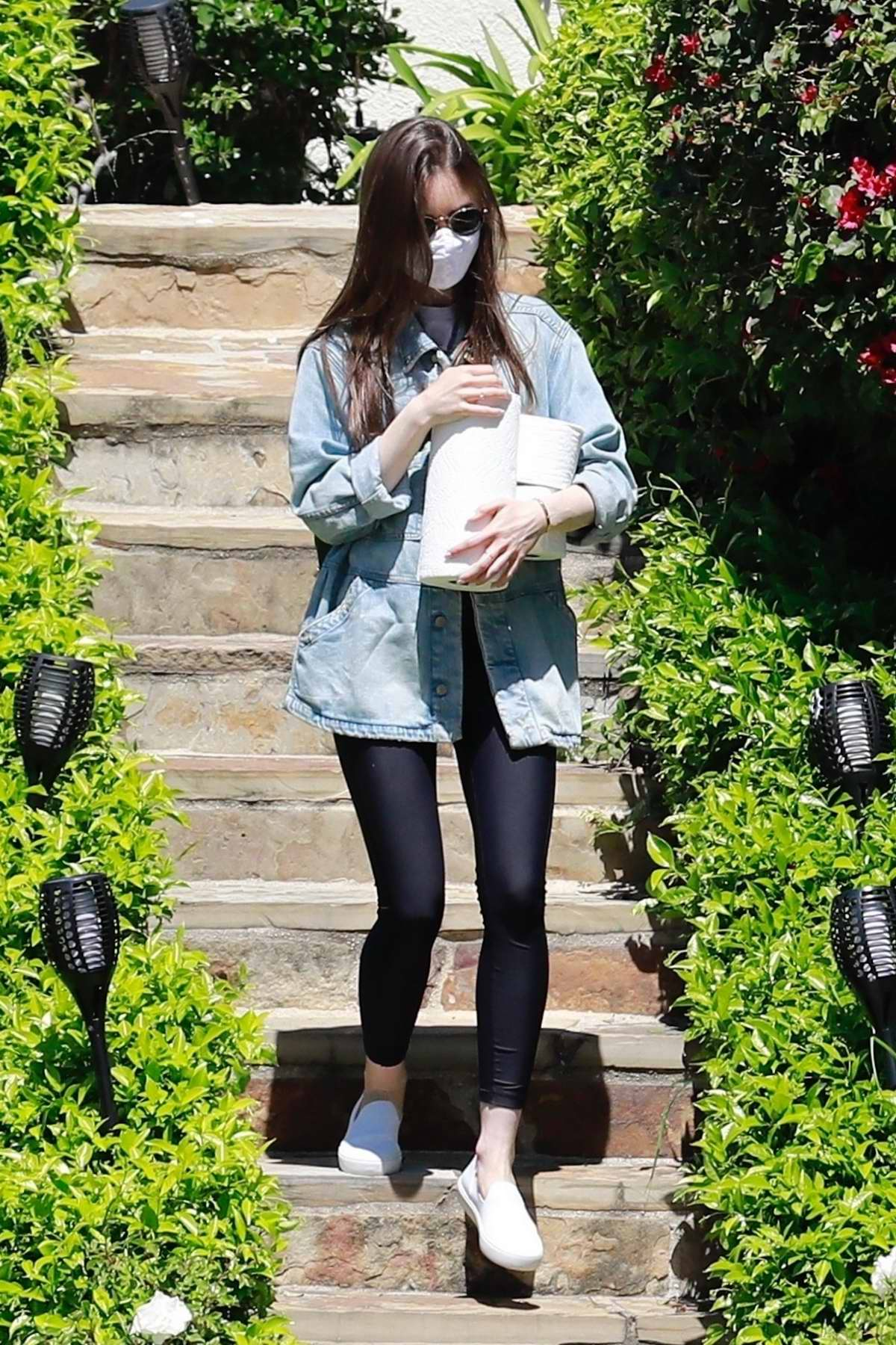 Lily Collins picks up some toilet paper rolls while visiting a family member in Los Angeles