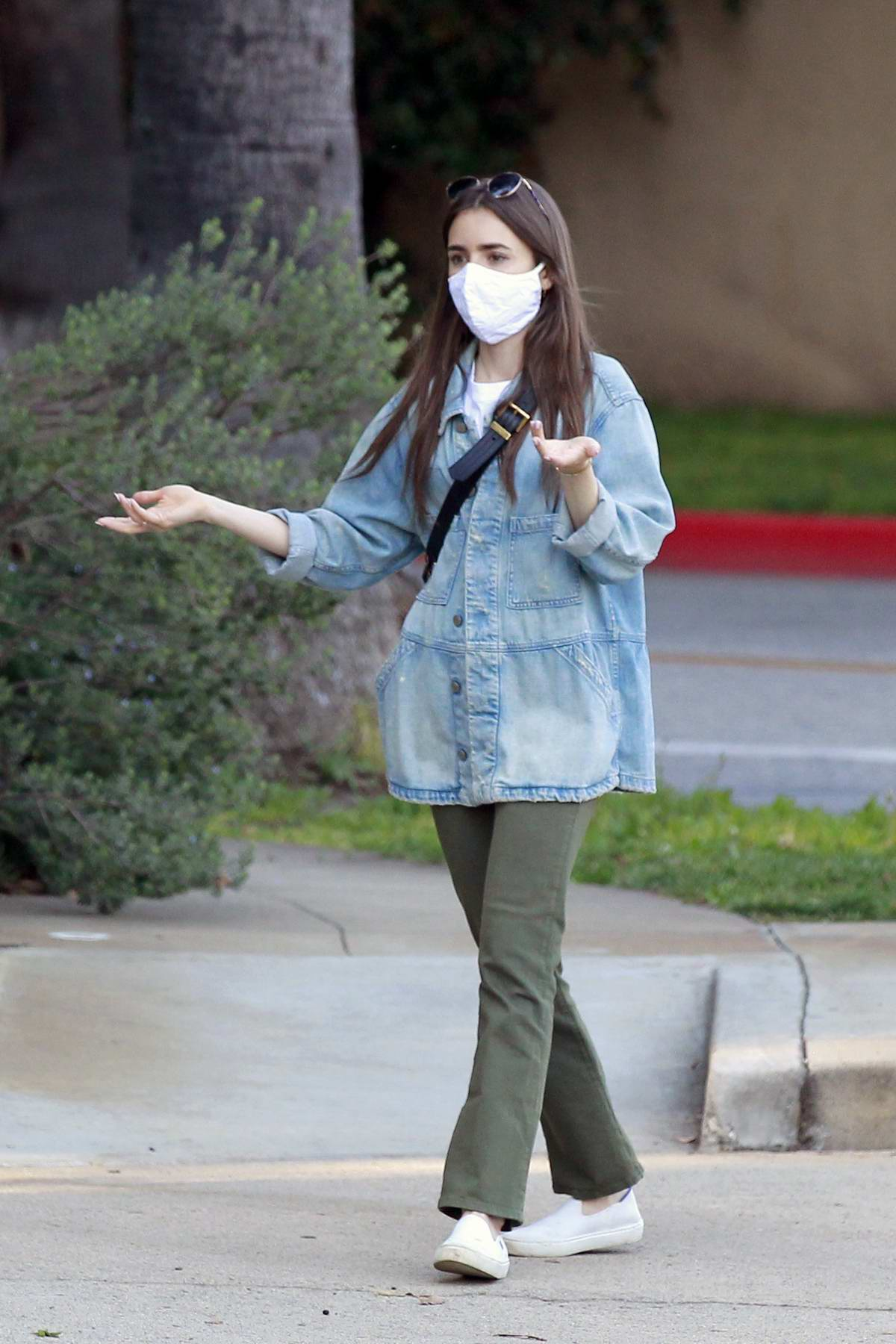 Lily Collins seen wearing a mask as she walks around her neighborhood in Beverly Hills, California