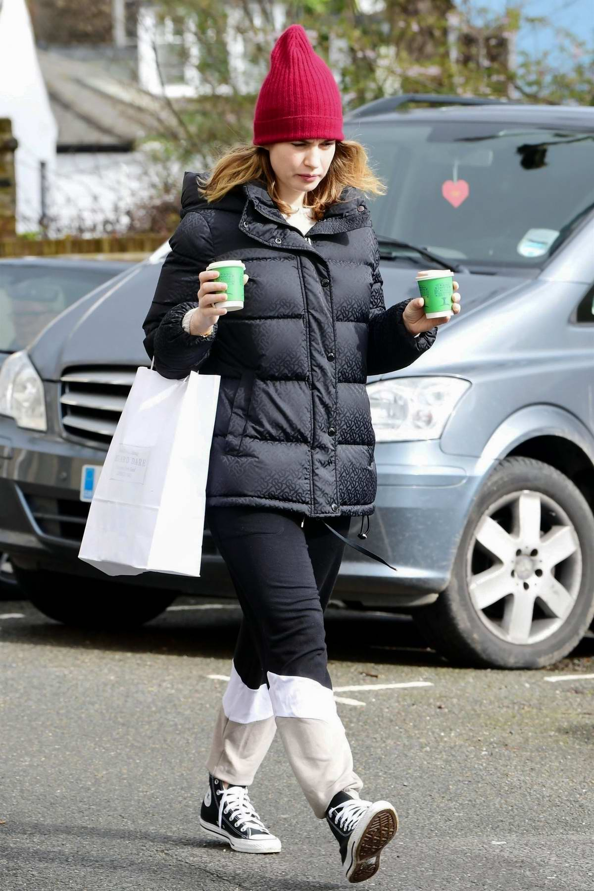 Lily James bundles up in a puffer jacket and a beanie while making a coffee run in London, UK