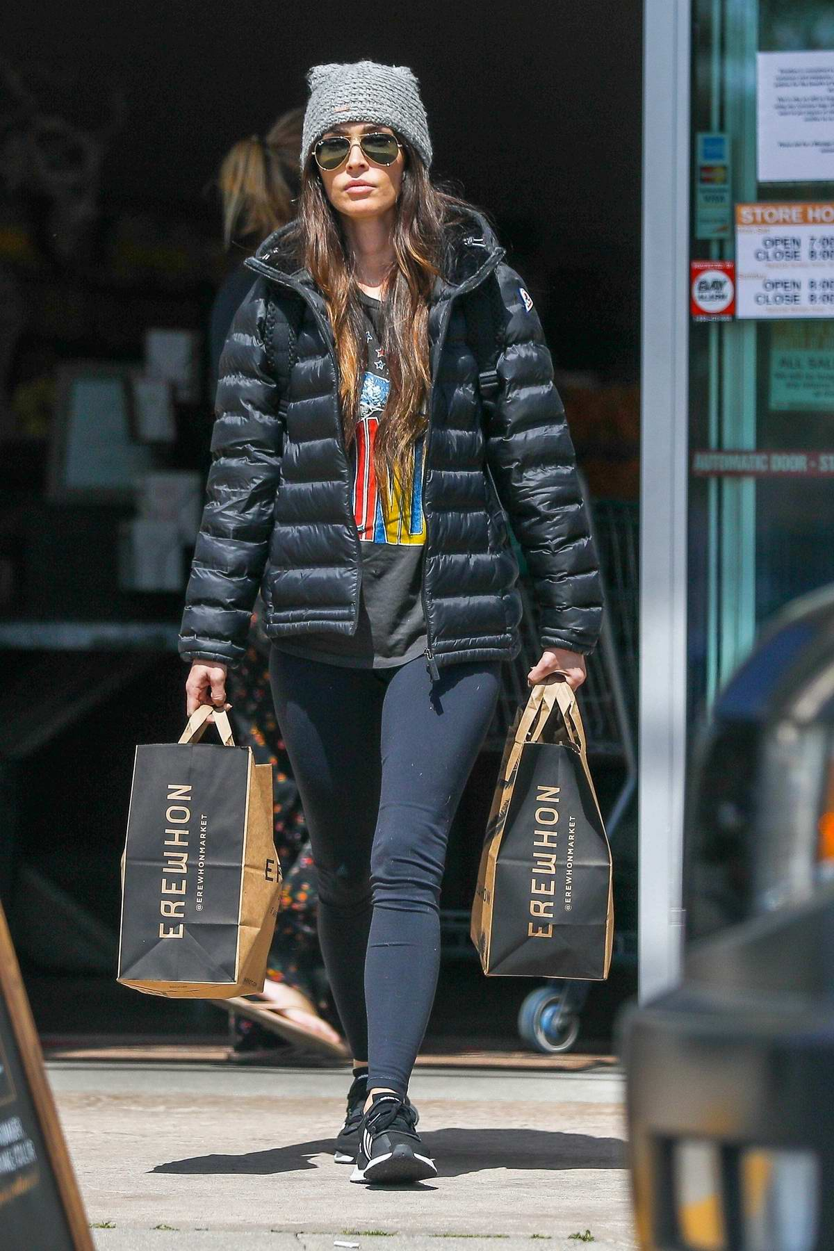 Megan Fox rocks aviator sunglasses with a beanie, puffy jacket and leggings during a grocery run at Erewhon in Los Angeles