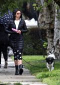 Nina Dobrev wears a puffer jacket and polka dot leggings as she steps out in the rain to walk her dog in Los Angeles