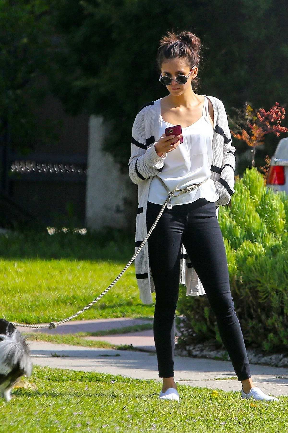 Nina Dobrev wraps the dog leash around her waist while out to walk her dog in Los Angeles