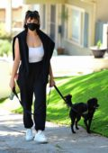 Rebecca Black covers up with a face mask walking her puppy in Orange County, California