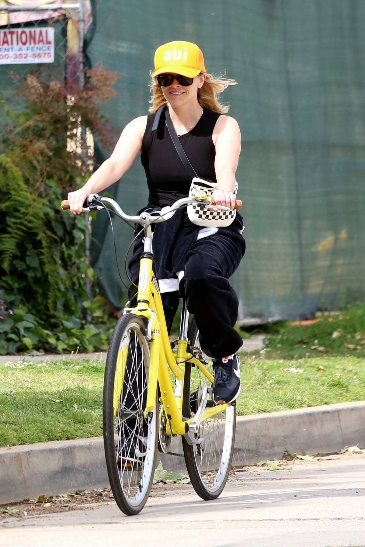 Reese Witherspoon goes for a power walk before riding a bicycle through the neighborhood in Pacific Palisades, California
