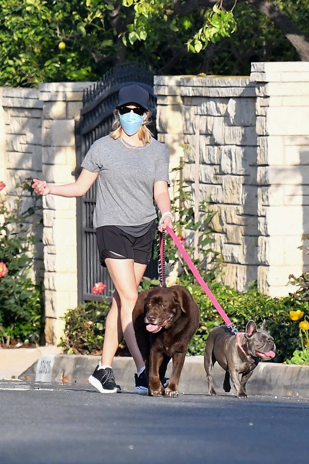Reese Witherspoon wears a tee and shorts as she takes her dogs for a walk in Brentwood, California