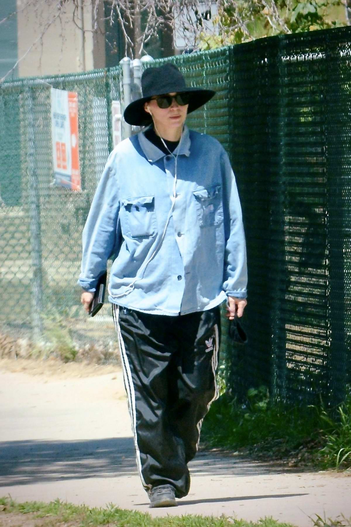 Rooney Mara wears a denim shirt and Adidas track pants with a fedora as she goes for a walk in Los Angeles