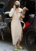 Sofia Richie wears a beige wrap dress and a mask as she arrives at her beach house with her dog in Malibu, California