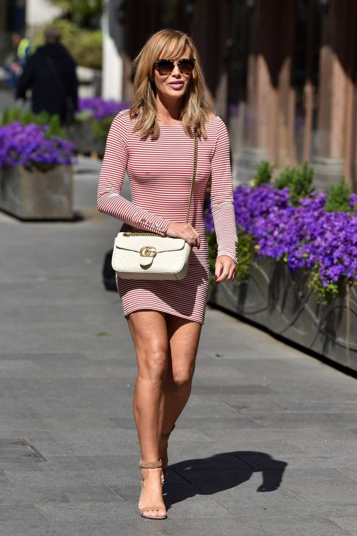 Amanda Holden wears a form-fitting striped mini dress while leaving the Global Radio Studios in London, UK