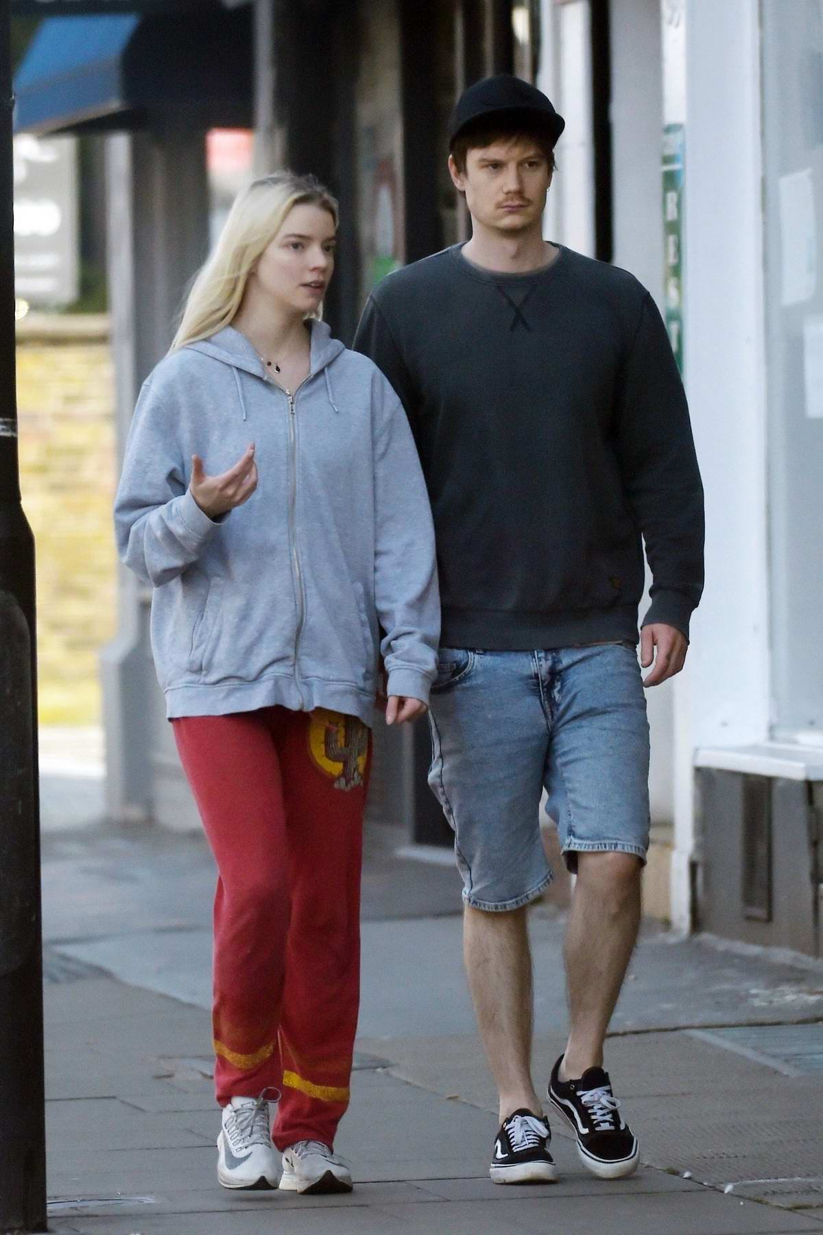 Anya Taylor-Joy dresses down in a grey hoodie and red sweatpants while out with boyfriend Ben Seed in London, UK