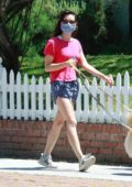 Aubrey Plaza wears a pink top and blue shorts as she steps out to walk her dogs in Los Angeles