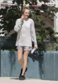 Cara Delevingne is all smiles as she chats on her phone while out for a walk in Los Angeles