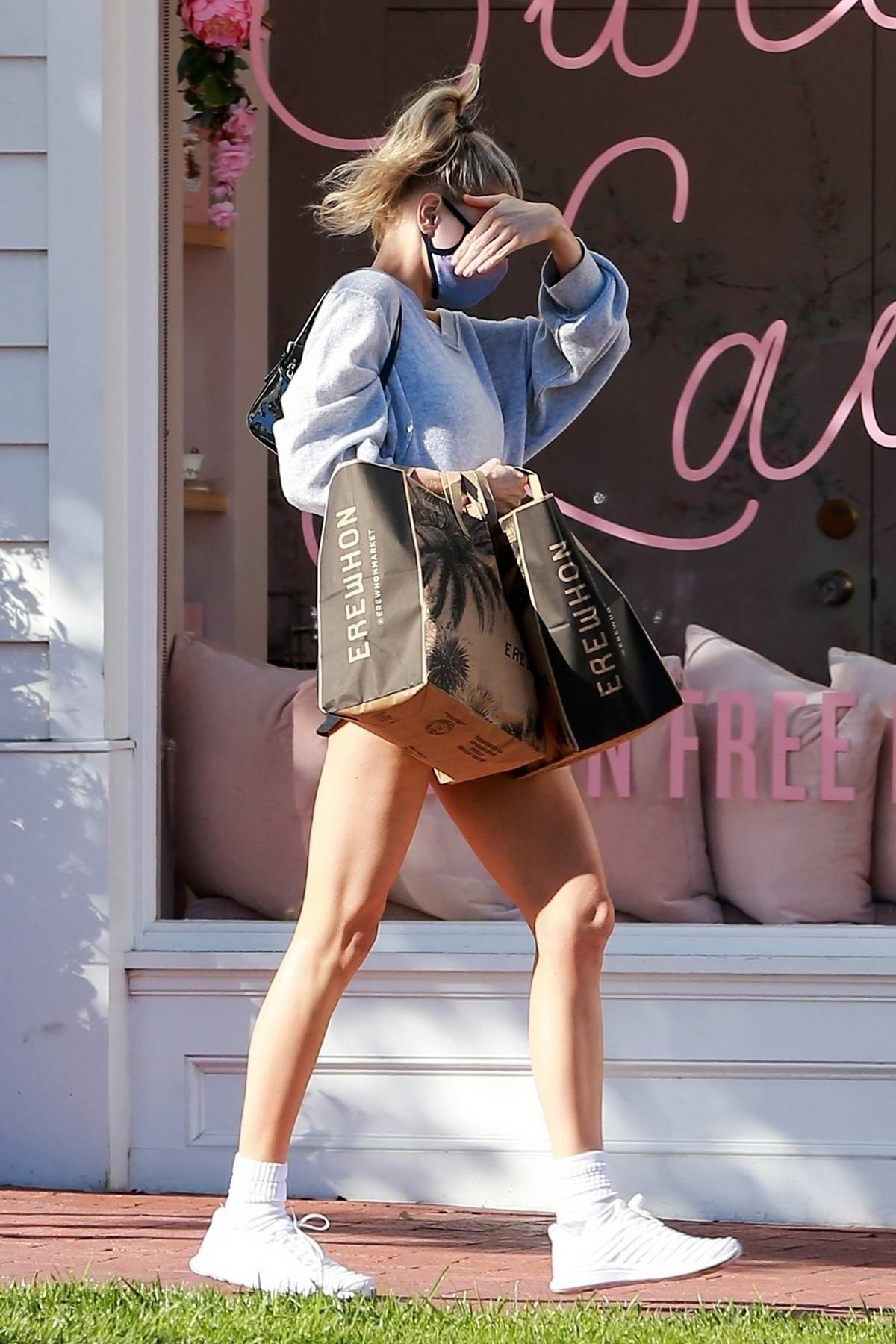 Charlotte McKinney flaunts her long legs while covering her face as she leaves Erewhon in Santa Monica, California