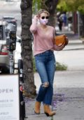 Emma Roberts looks trendy in a pink sweater, ripped jeans and suede boots during a coffee run in Los Angeles