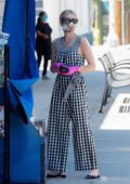 Emma Roberts seen wearing a checkered jumpsuit while stopping by a local newsstand in Studio City, California