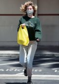 Ireland Baldwin wears socks and sandals while grocery shopping with a puppy-print face mask in Los Angeles