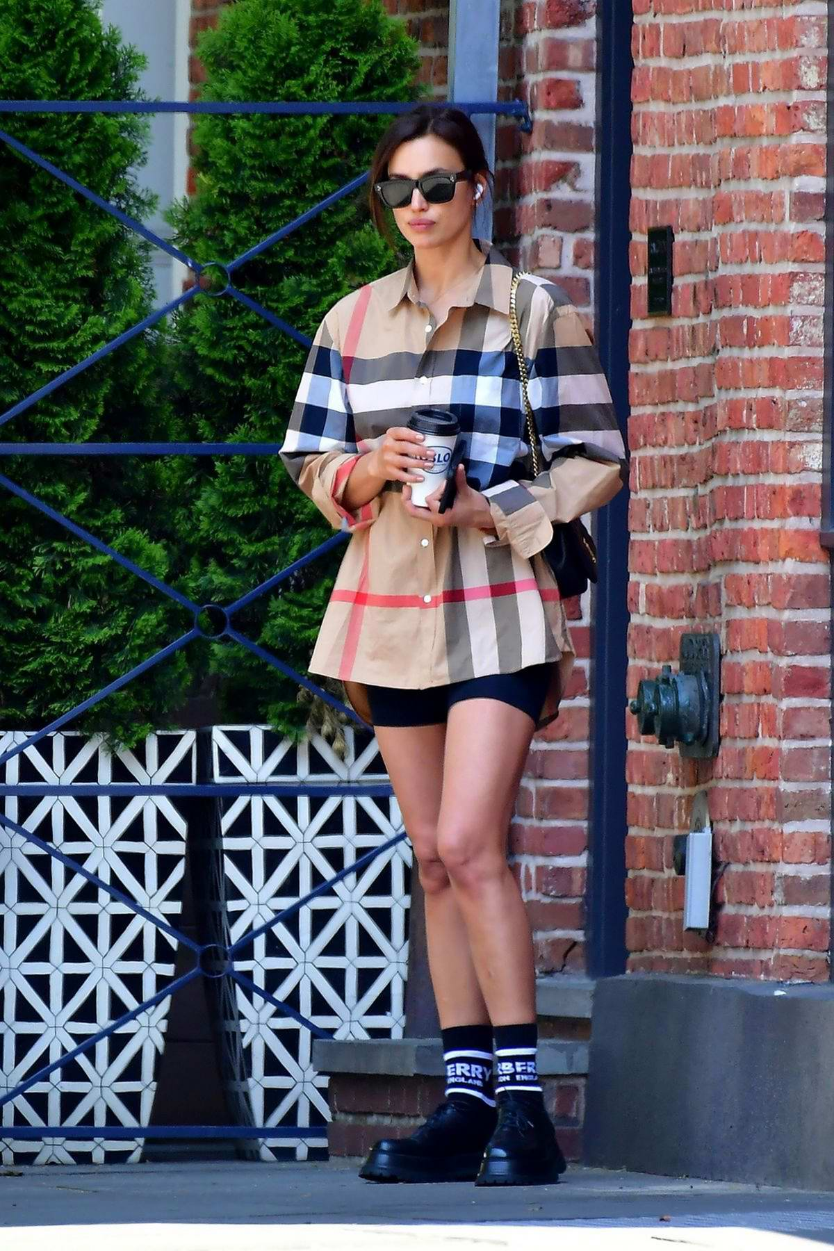 Irina Shayk keeps it chic in a Burberry shirt and black shorts while visiting Bradley Cooper's home in New York City