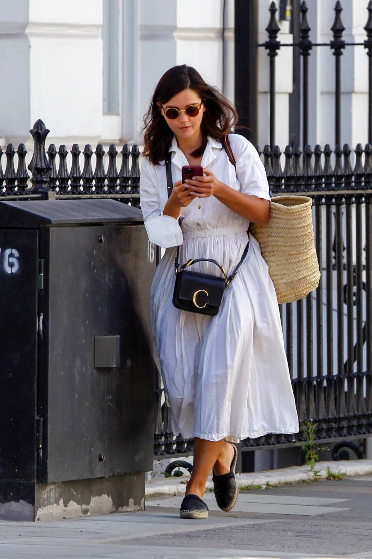 Jenna Coleman looked busy on her phone while out wearing a white dress in Central London, UK