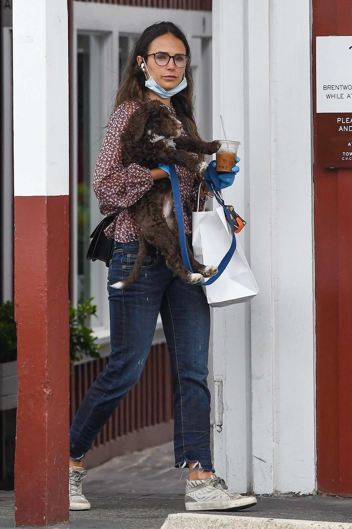 Jordana Brewster cradles her pup while out running errands in Brentwood, California