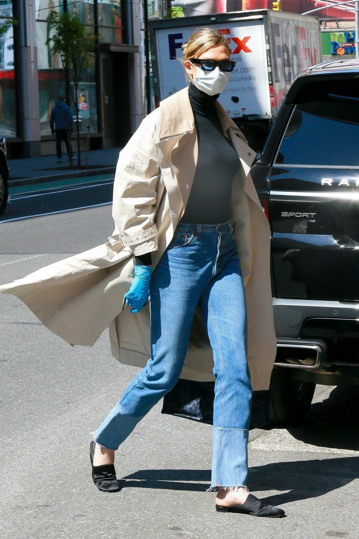 Karlie Kloss looks great in a black turtleneck, jeans and trench coat as she arrives back to her apartment in New York City
