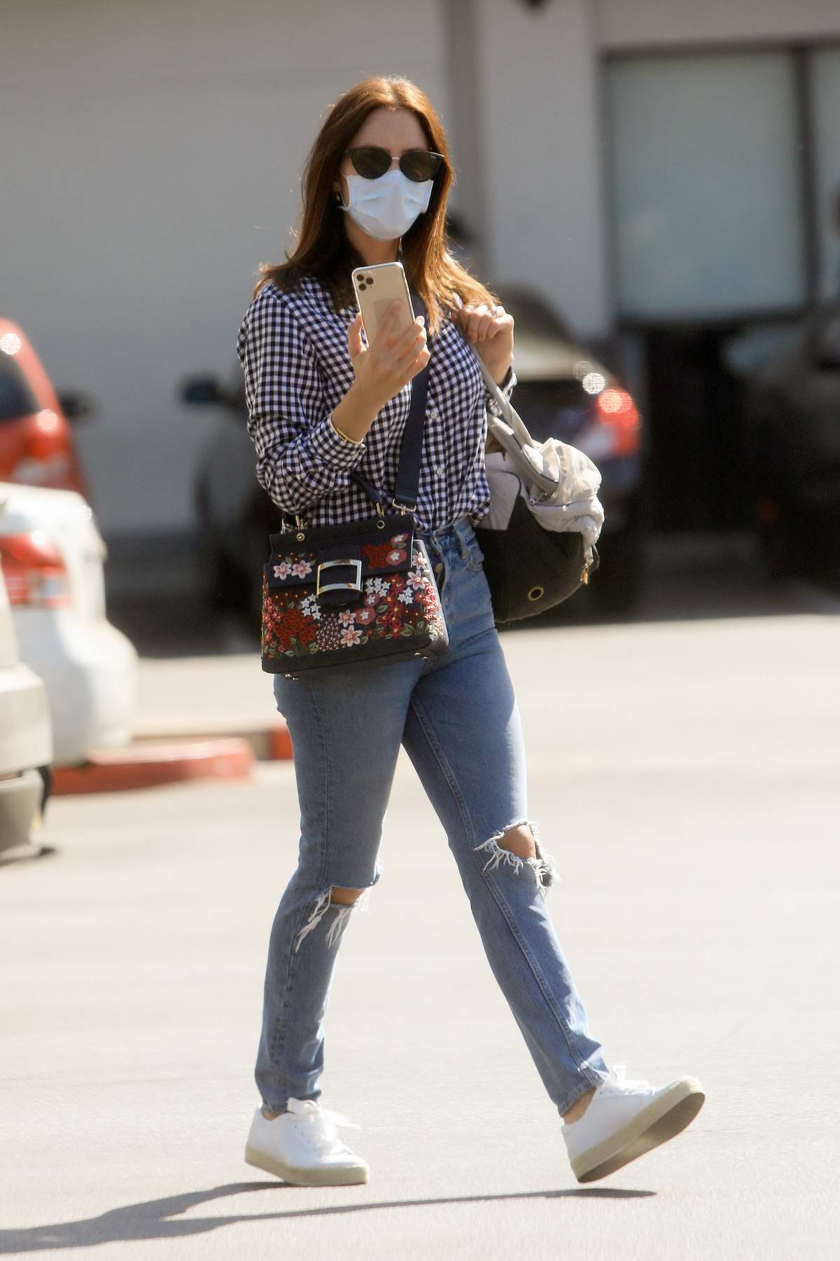 Katharine McPhee wears a checkered shirt, ripped blue jeans and a face mask while heading out in Los Angeles