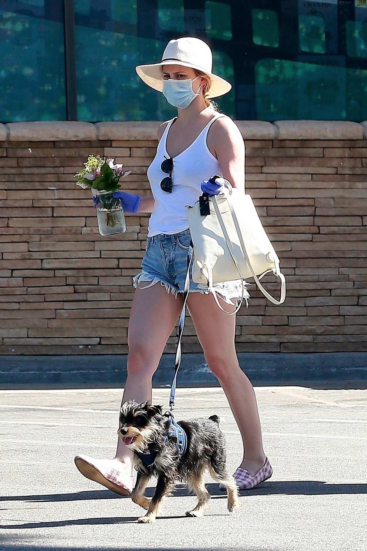 Lili Reinhart rocks a tank top and denim shorts as she takes her pup out for walk in Los Angeles