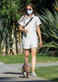 Lily Collins wears a beige romper as she goes for a masked stroll with her pooch in Beverly Hills, California