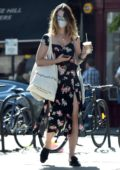 Lily James looks great in a black floral print dress as she picks up some groceries in Primrose Hill, London, UK