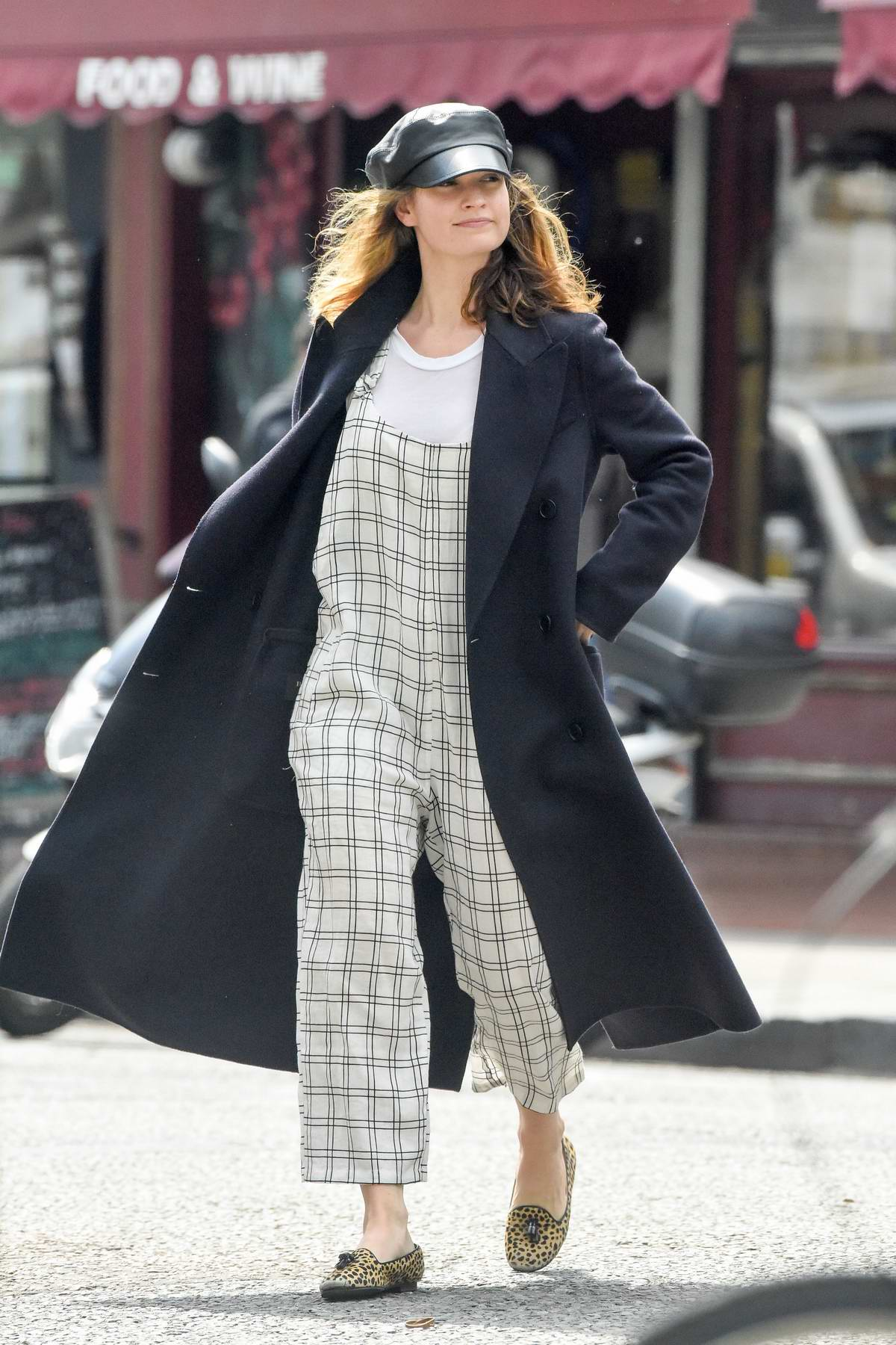 Lily James wears an overall and a long coat while out running errands in London, UK