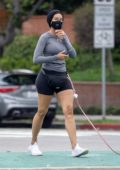 Nicole Murphy wears a grey top and short shorts while out to walk her dogs in Santa Monica, California