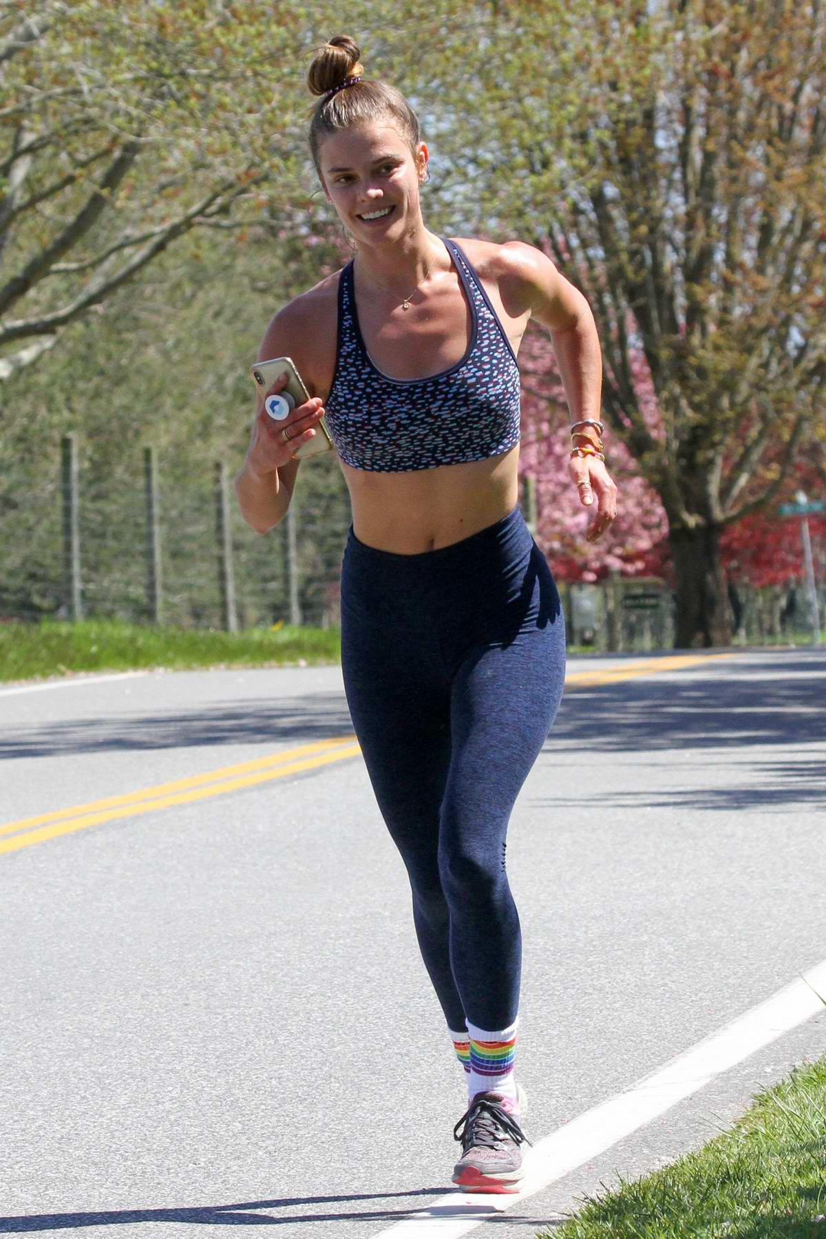 Nina Agdal shows off her fit figure in a crop top and leggings while out for a run in The Hamptons, New York