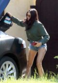 Nina Dobrev displays her long legs in denim shorts as she returns after a quick shopping trip in Los Angeles