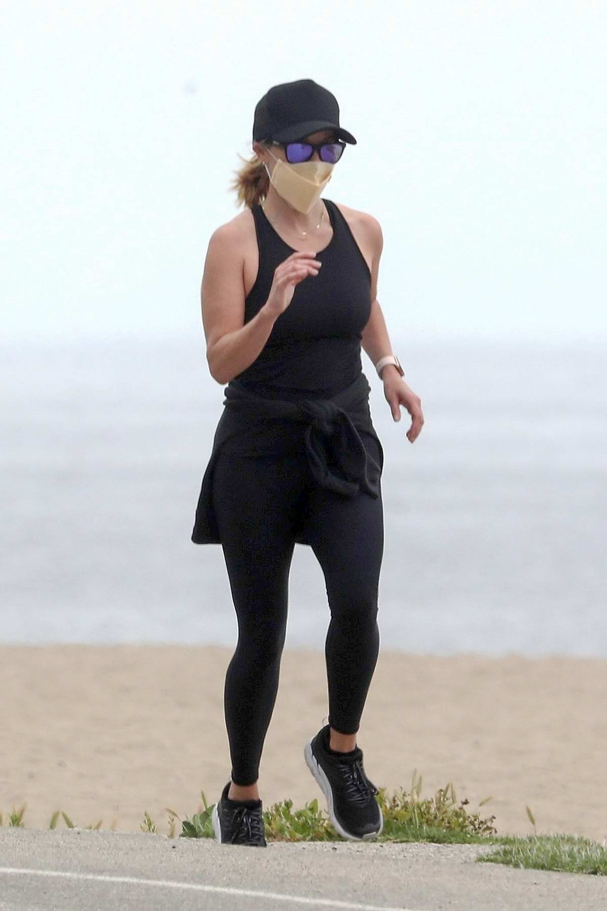 Reese Witherspoon sports all-black and a face mask while out for a jog with a friend in Malibu, California