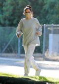 Selena Gomez wears a protective mask with a sweatshirt while out for a short walk with a friend in Los Angeles