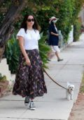 Ana de Armas wears a white top and printed long skirt as she takes her pooch out for a stroll in Santa Monica, California