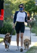Aubrey Plaza wears a crop top and legging shorts while walking her dogs in Los Feliz, California