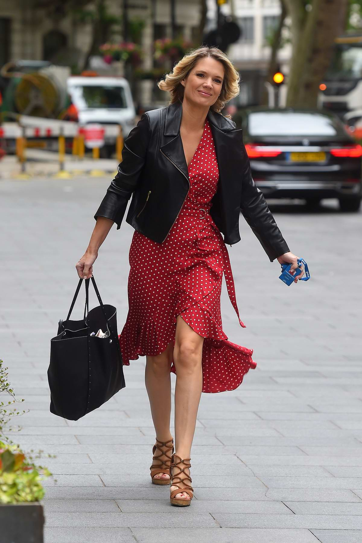 Charlotte Hawkins wears a red and white polka dot dress with a leather jacket as she arrives at Global Radio in London, UK