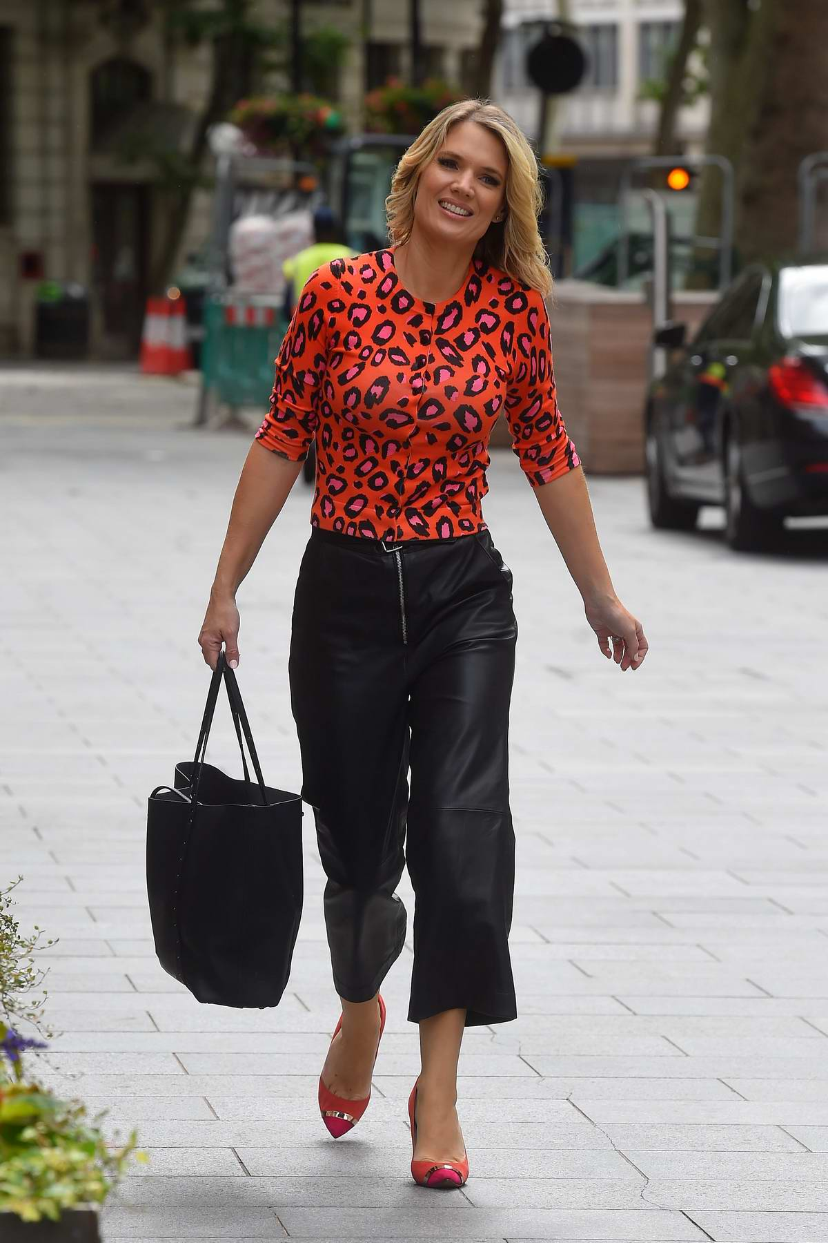 Charlotte Hawkins wears a red top and black leather pants as she arrives at the Global Radio studios in London, UK