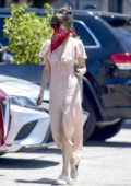 Dakota Johnson looks pretty in a button-down pink dress with Gucci sneakers while out running errands in Los Angeles