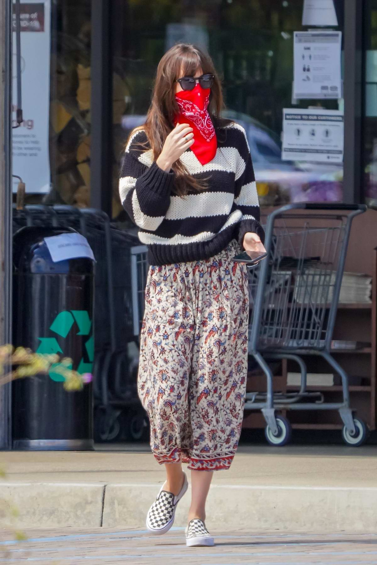 Dakota Johnson wears a floral print skirt and striped sweater as she picks up groceries in Malibu, California